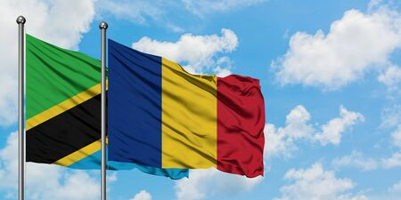 Tanzania and Romania flag waving in the wind against white cloudy blue sky together. Diplomacy concept, international relations. Stock Photo