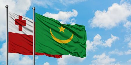 Tonga and Mauritania flag waving in the wind against white cloudy blue sky together. Diplomacy concept, international relations.