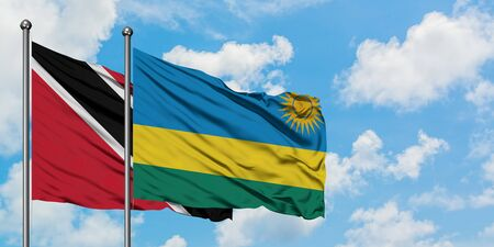 Trinidad And Tobago and Rwanda flag waving in the wind against white cloudy blue sky together. Diplomacy concept, international relations. Archivio Fotografico