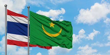 Thailand and Mauritania flag waving in the wind against white cloudy blue sky together. Diplomacy concept, international relations. Фото со стока
