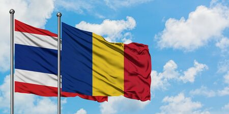 Thailand and Romania flag waving in the wind against white cloudy blue sky together. Diplomacy concept, international relations. Stock Photo