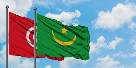 Tunisia and Mauritania flag waving in the wind against white cloudy blue sky together. Diplomacy concept, international relations.