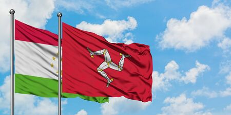 Tajikistan and Isle Of Man flag waving in the wind against white cloudy blue sky together. Diplomacy concept, international relations.