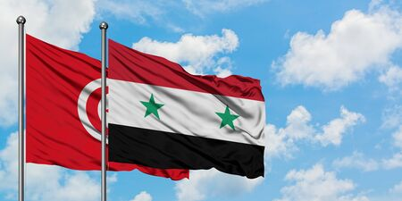 Tunisia and Syria flag waving in the wind against white cloudy blue sky together. Diplomacy concept, international relations.