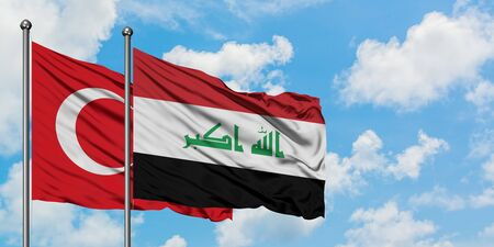 Turkey and Iraq flag waving in the wind against white cloudy blue sky together. Diplomacy concept, international relations. Reklamní fotografie