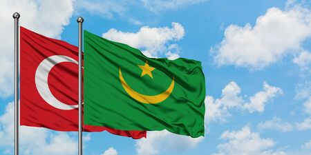Turkey and Mauritania flag waving in the wind against white cloudy blue sky together. Diplomacy concept, international relations.