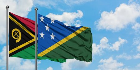 Vanuatu and Solomon Islands flag waving in the wind against white cloudy blue sky together. Diplomacy concept, international relations.