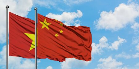 Vietnam and China flag waving in the wind against white cloudy blue sky together. Diplomacy concept, international relations. Stock Photo