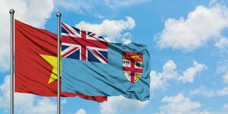 Vietnam and Fiji flag waving in the wind against white cloudy blue sky together. Diplomacy concept, international relations. Stock Photo