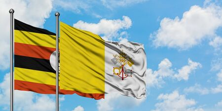 Uganda and Vatican City flag waving in the wind against white cloudy blue sky together. Diplomacy concept, international relations.