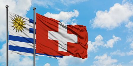 Uruguay and Switzerland flag waving in the wind against white cloudy blue sky together. Diplomacy concept, international relations.