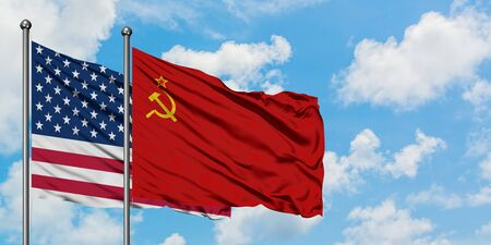 United States and Soviet Union flag waving in the wind against white cloudy blue sky together. Diplomacy concept, international relations.