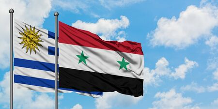 Uruguay and Syria flag waving in the wind against white cloudy blue sky together. Diplomacy concept, international relations.