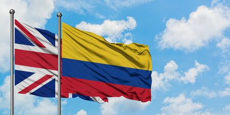 United Kingdom and Colombia flag waving in the wind against white cloudy blue sky together. Diplomacy concept, international relations.