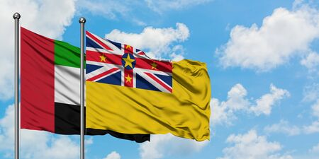 United Arab Emirates and Niue flag waving in the wind against white cloudy blue sky together. Diplomacy concept, international relations. Stock Photo