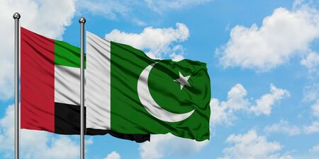 United Arab Emirates and Pakistan flag waving in the wind against white cloudy blue sky together. Diplomacy concept, international relations.