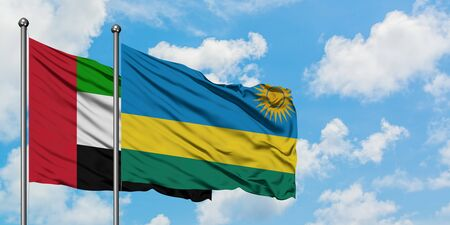 United Arab Emirates and Rwanda flag waving in the wind against white cloudy blue sky together. Diplomacy concept, international relations.