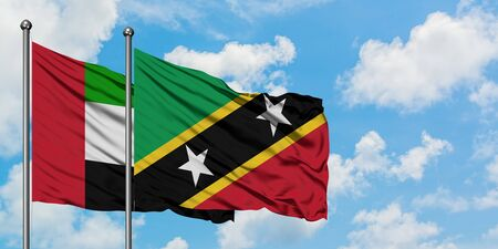United Arab Emirates and Saint Kitts And Nevis flag waving in the wind against white cloudy blue sky together. Diplomacy concept, international relations.