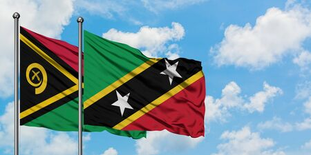 Vanuatu and Saint Kitts And Nevis flag waving in the wind against white cloudy blue sky together. Diplomacy concept, international relations. Stock fotó