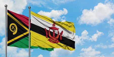Vanuatu and Brunei flag waving in the wind against white cloudy blue sky together. Diplomacy concept, international relations.