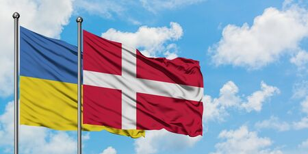 Ukraine and Denmark flag waving in the wind against white cloudy blue sky together. Diplomacy concept, international relations.