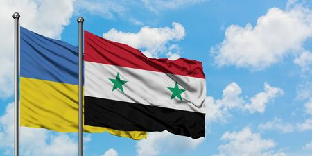Ukraine and Syria flag waving in the wind against white cloudy blue sky together. Diplomacy concept, international relations.