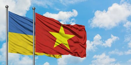 Ukraine and Vietnam flag waving in the wind against white cloudy blue sky together. Diplomacy concept, international relations.