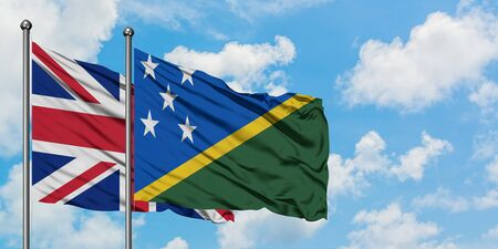 United Kingdom and Solomon Islands flag waving in the wind against white cloudy blue sky together. Diplomacy concept, international relations.