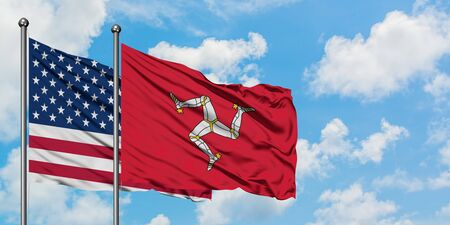 United States and Isle Of Man flag waving in the wind against white cloudy blue sky together. Diplomacy concept, international relations. Banque d'images