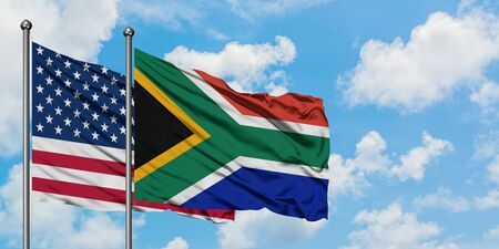 United States and South Africa flag waving in the wind against white cloudy blue sky together. Diplomacy concept, international relations.