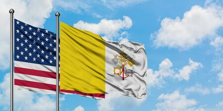 United States and Vatican City flag waving in the wind against white cloudy blue sky together. Diplomacy concept, international relations.