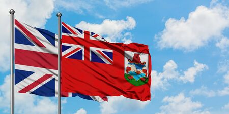 United Kingdom and Bermuda flag waving in the wind against white cloudy blue sky together. Diplomacy concept, international relations.
