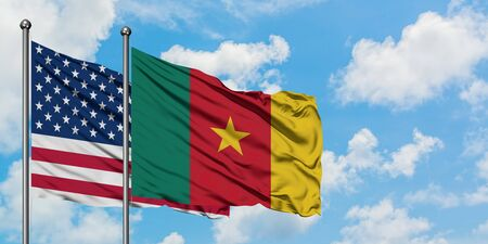 United States and Cameroon flag waving in the wind against white cloudy blue sky together. Diplomacy concept, international relations.