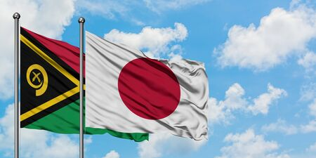 Vanuatu and Japan flag waving in the wind against white cloudy blue sky together. Diplomacy concept, international relations.