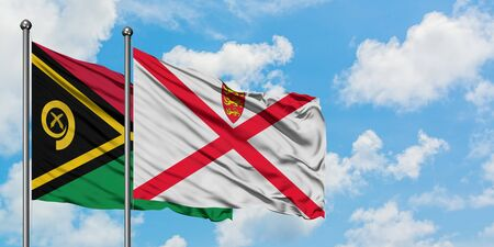 Vanuatu and Jersey flag waving in the wind against white cloudy blue sky together. Diplomacy concept, international relations. Stock fotó