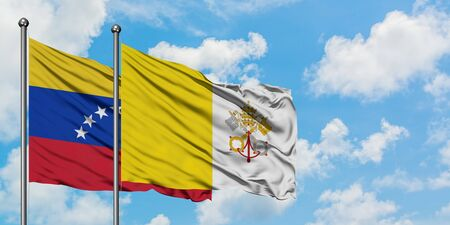 Venezuela and Vatican City flag waving in the wind against white cloudy blue sky together. Diplomacy concept, international relations.