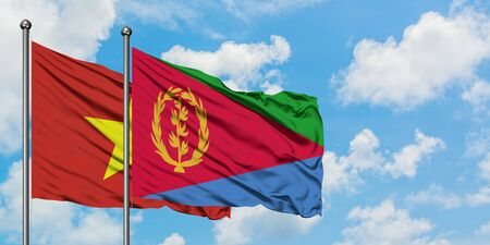 Vietnam and Eritrea flag waving in the wind against white cloudy blue sky together. Diplomacy concept, international relations.