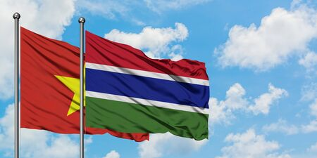 Vietnam and Gambia flag waving in the wind against white cloudy blue sky together. Diplomacy concept, international relations.