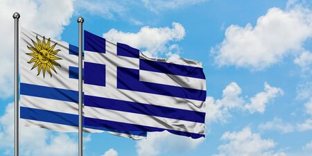 Uruguay and Greece flag waving in the wind against white cloudy blue sky together. Diplomacy concept, international relations. Standard-Bild