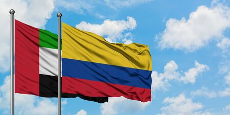 United Arab Emirates and Colombia flag waving in the wind against white cloudy blue sky together. Diplomacy concept, international relations.