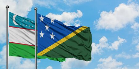 Uzbekistan and Solomon Islands flag waving in the wind against white cloudy blue sky together. Diplomacy concept, international relations.
