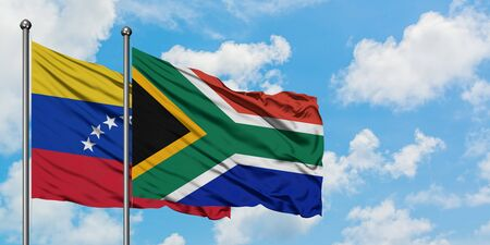 Venezuela and South Africa flag waving in the wind against white cloudy blue sky together. Diplomacy concept, international relations.