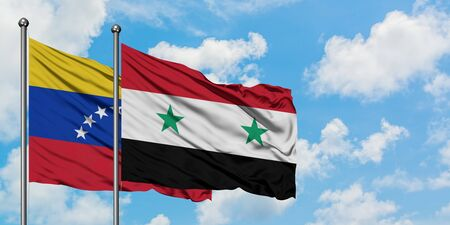 Venezuela and Syria flag waving in the wind against white cloudy blue sky together. Diplomacy concept, international relations.