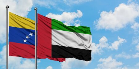 Venezuela and United Arab Emirates flag waving in the wind against white cloudy blue sky together. Diplomacy concept, international relations. Stock Photo