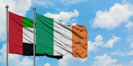 United Arab Emirates and Ireland flag waving in the wind against white cloudy blue sky together. Diplomacy concept, international relations.