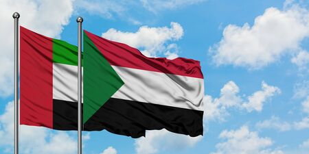 United Arab Emirates and Sudan flag waving in the wind against white cloudy blue sky together. Diplomacy concept, international relations.