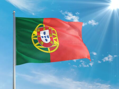 Portugal national flag waving in the wind against deep blue sky. High quality fabric. International relations concept.