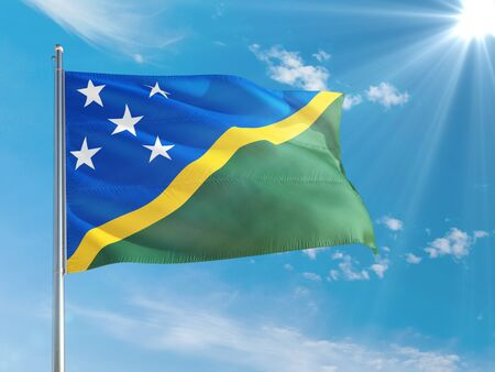 Solomon Islands national flag waving in the wind against deep blue sky. High quality fabric. International relations concept.