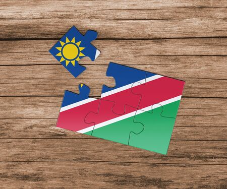 Namibia national flag on jigsaw puzzle. One piece is missing. Danger concept.