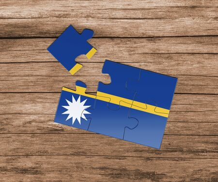 Nauru national flag on jigsaw puzzle. One piece is missing. Danger concept. 版權商用圖片
